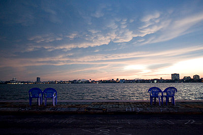 View of west lake (tay ho) at dusk. Blue plastic chairs and tables are arranged along the bank and face waters. Hanoi, Vietnam, Asia. - p934m832680 by Matthew Dakin