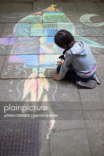 Mädchen malt Rakete auf Gehweg - p045m1588905 von Jasmin Sander