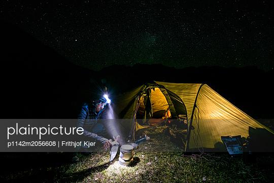 Camper kocht Abendessen in Dunkelheit  - p1142m2056608 von Runar Lind