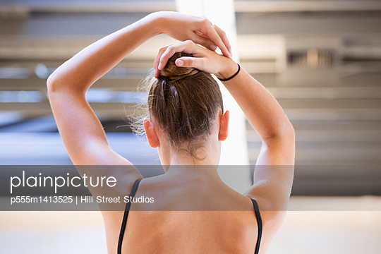 Ballet dancer tying hair in bun in studio