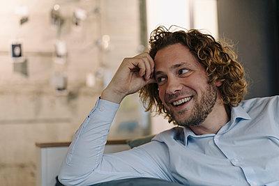 Portrait of happy businessman having a break in office - p300m2166878 by Kniel Synnatzschke