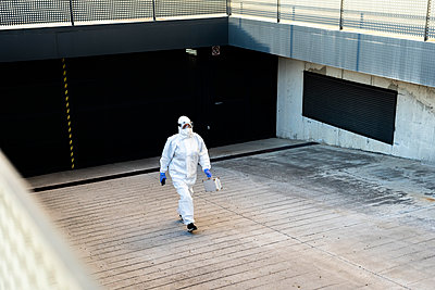 Female scientist wearing protective suit and mask and walking at a garage - p300m2170098 by Eloisa Ramos