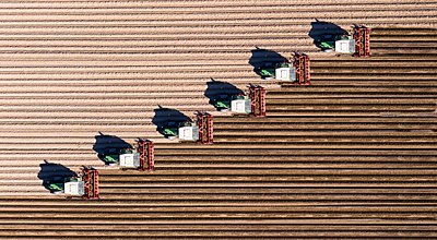 Germany, Hesse, Bergstarsse, Aerial view of tractors plowing brown field in spring - p300m2197312 by Martin Moxter