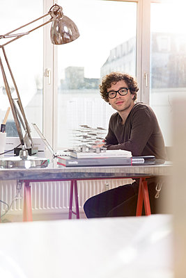 Portrait of young architect sitting at desktop in his office - p300m911177f by Florian Küttler