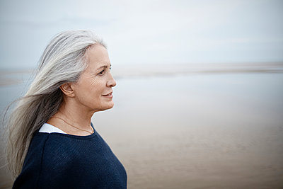 Pensive senior woman looking away on winter beach - p1023m1402937 by Great Images