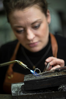 Female goldsmith heating ring with welding torch at workshop - p426m2097368 by Katja Kircher