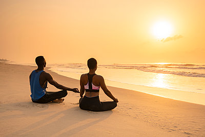 Couple practising yoga on beach - p429m2091817 by Ben Pipe Photography