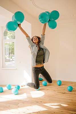 Young woman in new apartment playing with balloons - p586m1064905 by Kniel Synnatzschke