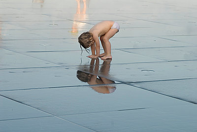 Girl looking in a water mirror - p681m904393 by Sandrine Léon