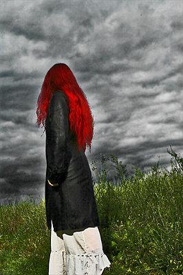 Frau mit roten Haaren auf einer Wiese - p9792396 von Vyge