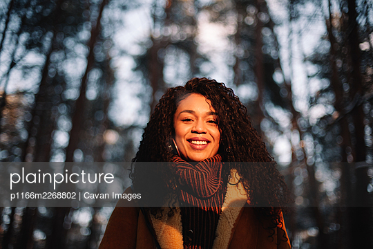 Portrait of smiling young woman standing amidst trees during winter - p1166m2268802 by Cavan Images