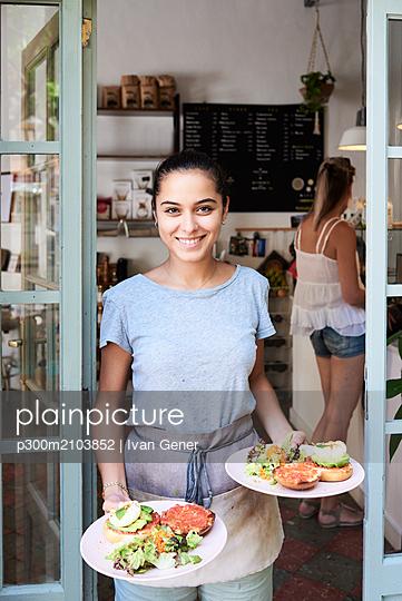 Portrait of smiling waitress serving breakfast - p300m2103852 by Ivan Gener