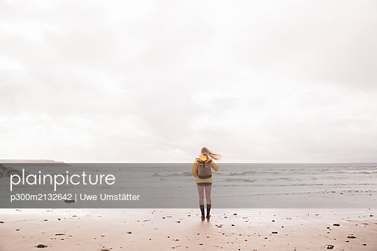 Rear view of woman wearing yellow rain jacket standing at beach - p300m2132642 by Uwe Umstätter