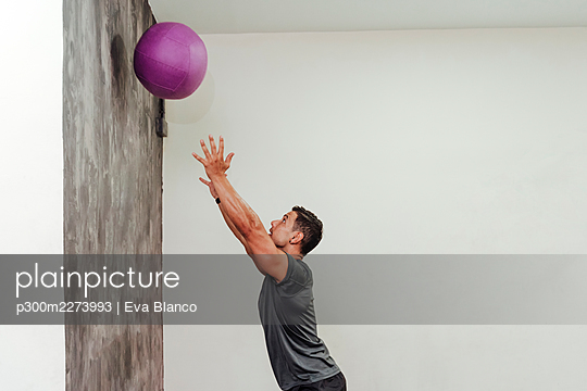 Mid adult male athlete exercising with medicine ball by wall at gym - p300m2273993 by Eva Blanco