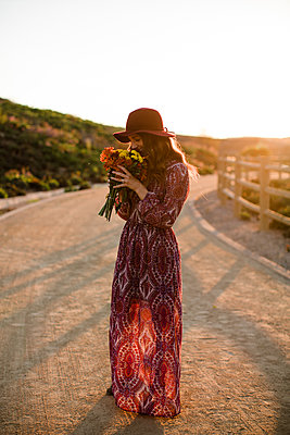 Young woman smiling and smelling flowers at sunset in SoCal - p1166m2095790 by Cavan Images