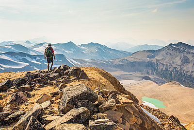 Backpacker hiking on mountain summit. - p1166m2153487 by Cavan Images