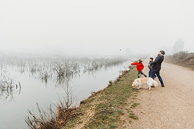 Father and two sons with dog throwing stones into lake on foggy day - p1166m2258276 by Cavan Images