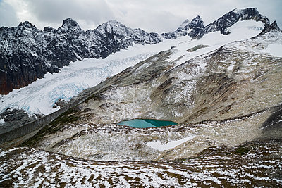 Glacial lake below snowy glacier and mountains, North West British Columbia, Canada - p1192m1213085 by Hero Images