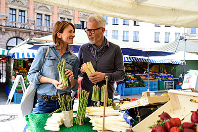 Mature couple choosing asparagus at a market stall - p300m2155724 by Eyecatcher.pro