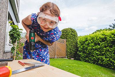 Girl wearing eyewear drilling on plank while standing in yard - p300m2202707 by Irina Heß
