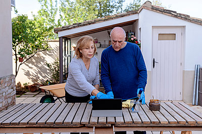 Senior couple using digital tablet while standing at backyard - p300m2273586 by Albert Martínez