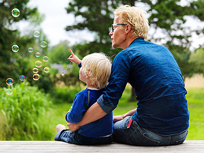 Father and son admiring bubbles outdoors - p42918040f by Henrik Weis