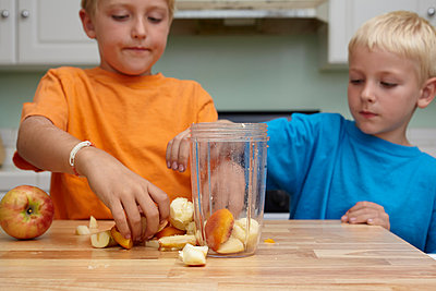Brothers blending fruits in kitchen - p429m976411 by Rachael Porter