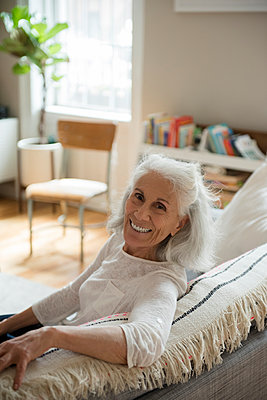 Portrait of smiling older woman on sofa - p555m1491477 by JGI/Jamie Grill