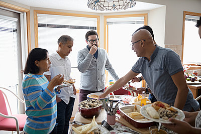 Latinx family enjoying buffet dinner in kitchen - p1192m2034537 by Hero Images