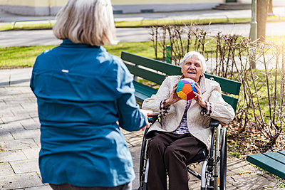 Woman taking care of old woman in wheelchair playing with ball in park - p300m1587885 by Daniel Ingold
