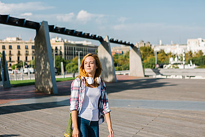 Young woman looking away with headphone around her neck walking on footpath during sunny day - p300m2226703 by Xavier Lorenzo