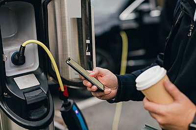 Midsection of man using smart phone at electric car charging station - p426m2195299 by Maskot