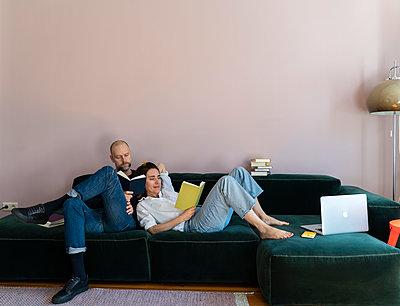 Paar mit Büchern auf dem Sofa - p432m2176121 von mia takahara
