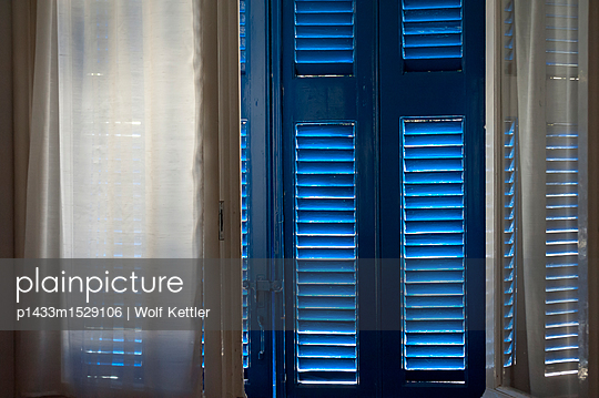 The midday sun shining through wooden shutters. - p1433m1529106 by Wolf Kettler