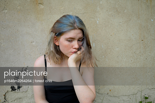 Young woman cups her chin in her hand - p1646m2264264 by Slava Chistyakov