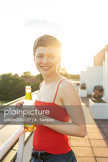 Smiling woman with beer bottle standing in balcony against clear sky during sunset - p300m2203127 by A. Tamboly