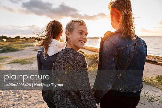 Smiling teenager looking away while standing with mother and daughter at beach - p426m2205426 by Kentaroo Tryman