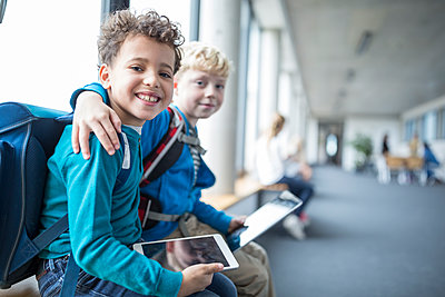 Portrait of two smiling schoolgboys with tablet embracing - p300m2005294 von Fotoagentur WESTEND61