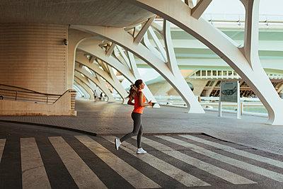 Spain, Valencia, woman running at Ciudad de las Artes y de Las Ciencias - p300m2060227 by Javier Pardina