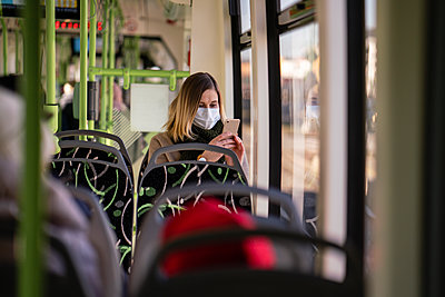 Woman with face mask sitting in tram, using smartphone - p300m2170849 by Vasily Pindyurin