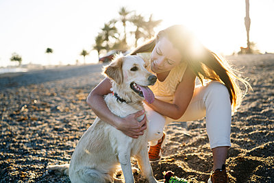 Smiling woman embracing dog while on sand during sunny day at weekend - p300m2267792 by Manu Padilla Photo