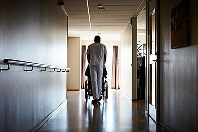 Full length rear view of male nurse pushing senior man on wheelchair at hospital corridor - p426m1494022 by Maskot