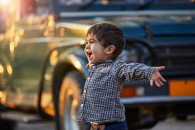 Excited toddler with open arms standing by a large vehicle - p429m2164646 by Sverre Haugland
