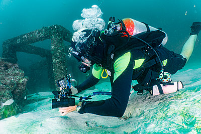 Scuba diver inspecting concrete structures placed in ocean to create living space for marine life - p924m2145359 by Henn Photography