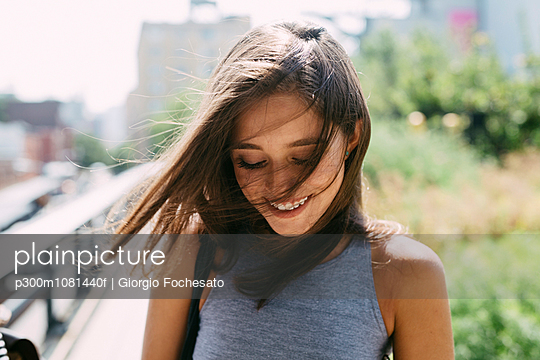 USA, New York City, smiling brunette young woman outdoors - p300m1081440f by Giorgio Fochesato