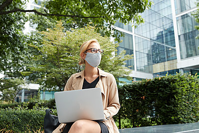 Woman wearing face mask using laptop while sitting at office park in city - p300m2227062 by Pete Muller