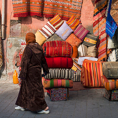 A woman walks past colourful cushions and textiles on display; Marrakesh, Marrakech-Tensift-El Haouz, Morocco - p442m824162 by Keith Levit