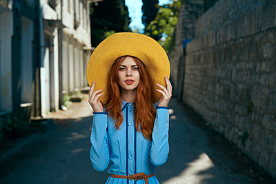 Smiling Caucasian woman wearing hat near stone wall - p555m1504220 by Dmitry Ageev