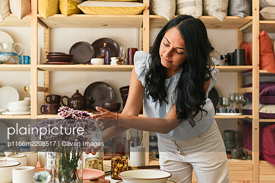 Woman checking the price and detail of artisan home goods in store - p1166m2208517 by Cavan Images