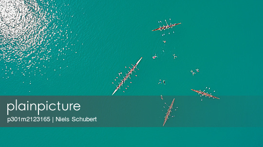 Aerial view scull boats and swimmers in sunny, turquoise Lake Geneva, Cully, Vaud, Switzerland - p301m2123165 by Niels Schubert